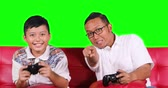 Happy little boy and his father playing a video game and celebrate the winning together by clapping hands or making a high five gesture, shot in 4k resolution