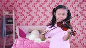 Adorable little girl with pigtail hair, playing a violin in the bedroom with pink color decoration at home
