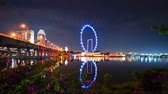 Singapore. October 30, 2017: Timelapse of Singapore Flyer at night with reflection on the water from Gardens By The Bay. Shot in 4k resolution