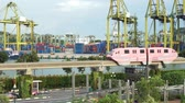 Singapore - November 28, 2017: Video footage of Sentosa Express Monorail with Singapore container port on the background