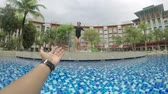 Video footage of a male hand invites his girlfriend to swim on the luxury hotel pool Vidéos Libres De Droits