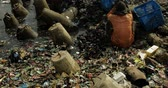 coletor : JAKARTA - Indonesia. March 29, 2018: Video footage of garbage man working to clean garbage on the beach with box. Shot in 4k resolution
