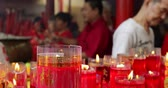 incenso : JAKARTA - Indonesia. March 26, 2018: Closeup of burning red candles with buddhist people background on Chinese New Year celebration in Chinese temple. Shot in 4k resolution