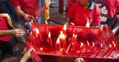 incenso : JAKARTA - Indonesia. March 26, 2018: Closeup of buddhist people hands burning incense sticks to pray on Chinese New Year celebration in Chinese temple. Shot in 4k resolution