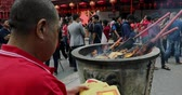 китайский квартал : JAKARTA - Indonesia. March 28, 2018: Chinese man burning paper money on the incense pot at Chinese New Year celebration in Chinatown of Glodok, Jakarta city. Shot in 4k resolution