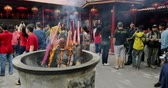 incenso : JAKARTA - Indonesia. March 28, 2018: Burning incense sticks on the pot with crowded people in Chinese temple at Chinatown of Glodok, Jakarta, Indonesia. Shot in 4k resolution
