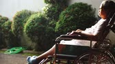 devaneio : Paralyzed old woman sunbathing for health on the morning while sitting on the wheelchair at nursing home Stock Footage