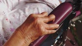 oneself : Palsied old woman hand with rigid fingers sitting on wheelchair at home