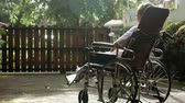 devaneio : Lonely paralyzed elderly woman sitting on wheelchair while sunbathing for health on the morning at home