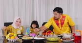 ramadan kareem : Young muslim man serving a plate of meals for his wife during dinner together with his family in dining room at home. Shot in 4k resolution during Ramadan Kareem Stock Footage
