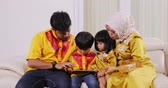ramadan kareem : Happy muslim family using a digital tablet while sitting on the sofa in the living room at home. Shot in 4k resolution during Ramadan Kareem Stock Footage
