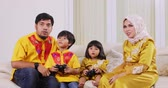 controlador : Two young muslim parents and their children playing video games together while sitting on the sofa at home. Shot in 4k resolution during Ramadan Kareem Vídeos