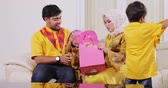 ramadan kareem : Happy muslim family open a gift bag while sitting on the sofa and wearing islamic clothes in living room at home. Shot in 4k resolution Stock Footage