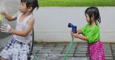 шланг : Two happy siblings washing car while playing water with a water hose at home. Shot in 4k resolution Стоковые видеозаписи