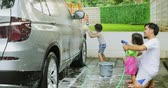 lánytestvér : Two cheerful kids and their father washing a car using a water hose and sponge at home. Shot in 4k resolution Stock mozgókép