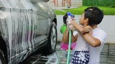 шланг : Slow motion of cheerful little boy and his father using a water hose to wash a car at home
