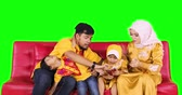 ramadan kareem : Happy muslim family relaxing together on the sofa while using a mobile phone in the living room at home. Shot in 4k resolution