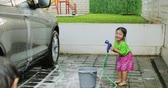 bratr : Happy little boy and his sister washing their car with a sponge and water hose at home. Shot in 4k resolution Dostupné videozáznamy
