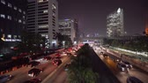 congestion : JAKARTA, Indonesia - June 22, 2018: Jakarta cityscape at night with skyscrapers and crowded cars on traffic jam. Shot in 4k resolution