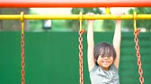 playground : Joyful Asian little girl playing on the swing at the park on summer day. Shot in 4k resolution Stock Footage
