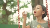 sopro : Asian little girl blowing soap bubbles while sitting on a swing at the park. Shot outdoors on summer time