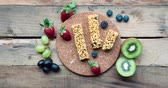 stopmotion : Stop motion of granola bar with fruits on the wooden table. Shot in 4k resolution