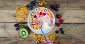 stopmotion : Stop motion of hand with a spoon taking cereal on a bowl over wooden table. Shot in 4k resolution Stock Footage