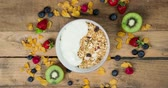 joghurt : Stop motion of organic homemade granola cereal with yogurt and fresh fruit slices on a bowl. Shot in 4k resolution