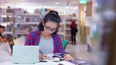 referência : Female college student studying in the library while writing on a book with bookshelf background. Shot in 4k resolution Vídeos