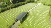 tomb : JAKARTA, Indonesia - October 09, 2018: Aerial landscape of Ereveld Menteng Pulo or Dutch war cemetery with crosses, pathway, and green grass in Jakarta, Indonesia. Stock Footage