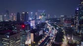 esquerda : JAKARTA, Indonesia - October 19, 2018: Beautiful aerial hyperlapse of skyscrapers at night with night traffic and beautiful night lights. Shot in 4k resolution