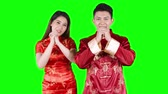 tebrik etmek : Happy Chinese New Year Concept. Asian couple congratulate Chinese New Year while wearing chinese traditional cheongsam. Shot in 4k resolution with green screen background