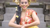 плюмерия : Beautiful female balinese dancer with traditional dress smiling and dancing in a hinduism temple. Shot in 4k resolution