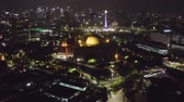 indonesia : JAKARTA, Indonesia - December 12, 2018: Beautiful aerial landscape of Istiqlal Mosque with skyscrapers and National Monument background at night. Shot in 4k resolution