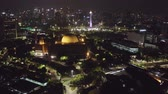 JAKARTA, Indonesia - December 12, 2018: Beautiful aerial scenery of Istiqlal Mosque with National Monument and skyscrapers at night. Shot in 4k resolution
