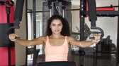 saco : Healthy young woman smiling at the camera while doing workout on exercise machine at gym. Shot in 4k resolution