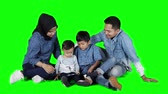 femme musulmane : Happy casual family using a mobile phone while sitting on the floor in the studio. Shot in 4k resolution with green screen background