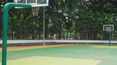 playground : Outdoor basketball court with two basket hoop and green trees background at the park. Shot in 4k resolution Stock Footage