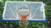 exercises : Outdoor basketball board and basket hoop with green trees background at the park. Shot in 4k resolution