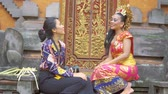 балийский : Balinese woman wearing traditional clothes and talking with a reporter or photographer while sitting in the temple. Shot in 4k resolution Стоковые видеозаписи