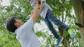 parentalidade : Cheerful young father lifting his son at the park. Shot outdoors in 4k resolution