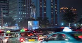 congestionamento : JAKARTA, Indonesia - February 11, 2019: Time lapse footage of traffic jam with crowded vehicles and Sudirman statue background at night on Sudirman street in Jakarta. Shot in 4k resolution