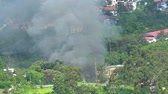 provocação : Smoke from burning garbage heap at the yard near residential houses. Shot in 4k resolution
