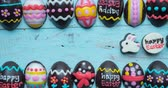 stopmotion : Stop motion of decorative chocolate easter eggs and easter rabbit with happy easter text on wooden table. Shot in 4k resolution