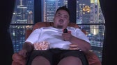 chamtivost : Overweight man watching TV while sitting on the sofa and eating snacks like popcorn and hamburger in apartment. Shot in 4k resolution Dostupné videozáznamy