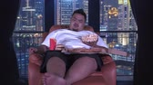 hamburguesa con queso : Young overweight man sits on sofa while eating junk foods likes popcorn, french fries, burger, and pizza in apartment. Shot in 4k resolution