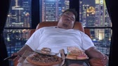 жадность : Bad habit concept. Gorged obese man sleeping on the sofa with junk foods after watching TV in his apartment. Shot in 4k resolution