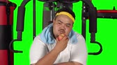 obezita : Overweight young man eating a fresh apple fruit while sitting on gym machine. Shot in 4k resolution