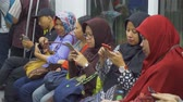 mrt : JAKARTA, Indonesia - March 26, 2019: Group of female passengers using smartphone while sitting in Mass Rapid Transit (MRT) subway train Jakarta. Shot in 4k resolution