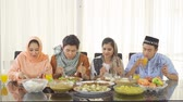 ketupat : Group of young happy muslim people break the fast together and eating Indonesian traditional foods on the table in dining room at home. Shot in 4k resolution